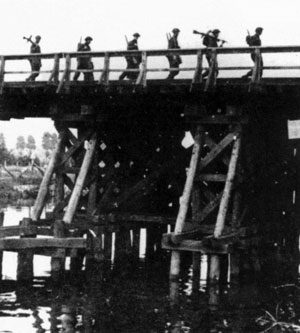 Guards Armoured Division infantry cross a wooden bridge