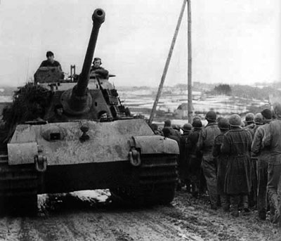 A Tiger II passes US prisoners