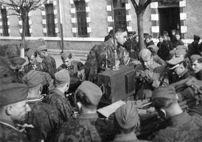 Waffen-SS members listen to a radio announcement