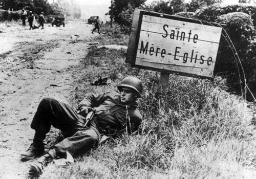 A US trooper poses by the Sainte Mere-Eglise road sign