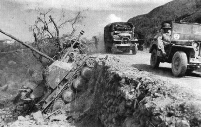 French forces advance through the mountains pass a knocked out Marder III H.