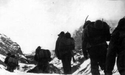A line of Monterosa Alpini marching on the snow-covered mountains.