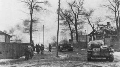 Das Reich troops advance through a burning village on the tail of retreating Soviets