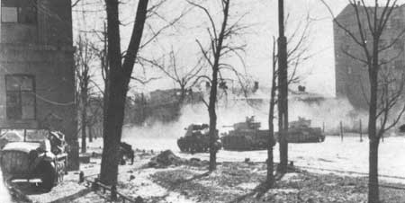 Two Panzer IVs and a Marder hammer away at some Soviet occupied buildings