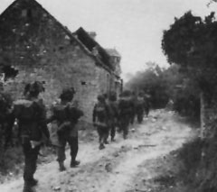 British infantry advance pass some farm buildings