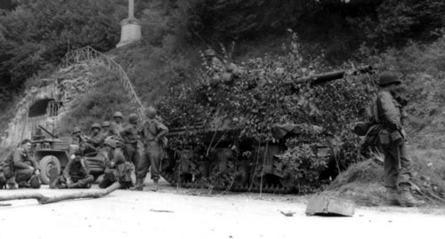 Camouflaged Sherman halts by a road