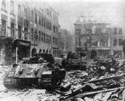 T-34 tanks adavnce through a city street after heavy fighting
