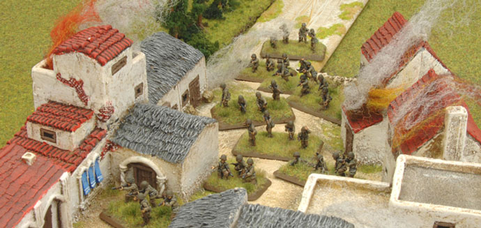 The Rifle platoon enters the village taking cover from the artillery fire.