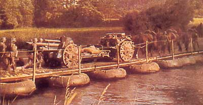 A leFH18, limber and horse team cross a pontoon bridge