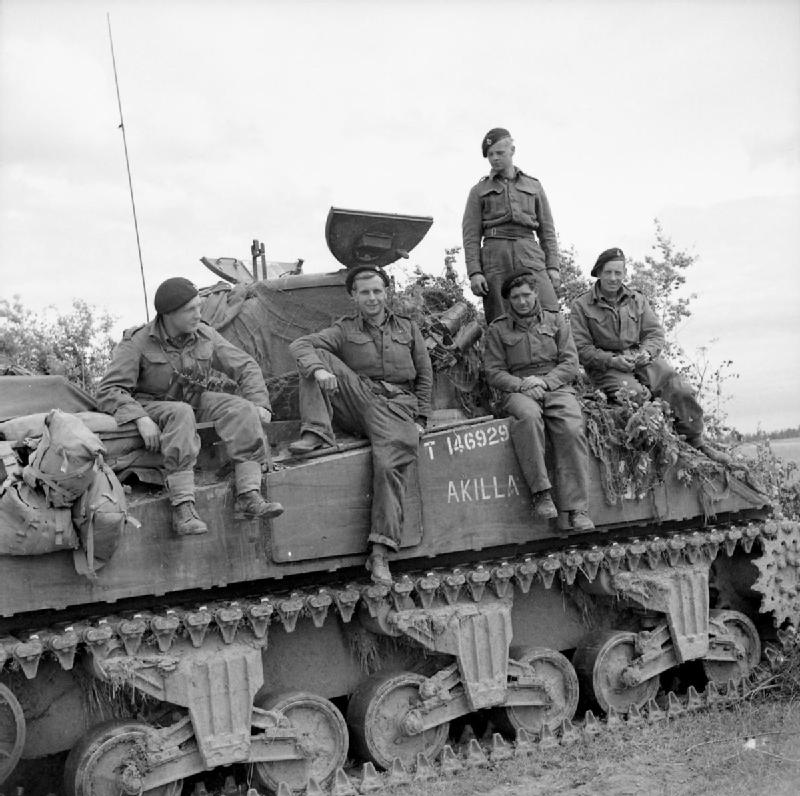 The crew of a Sherman tank named 'Akilla' of 1st Nottinghamshire Yeomanry, 8th Armoured Brigade, after having destroyed five German tanks in a day, Rauray, Normandy, 30 June 1944.